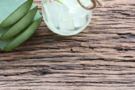 Fresh aloe vera leaves and glass of aloe vera juice on wooden background and have copy space.