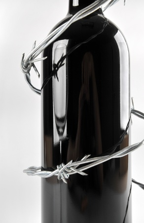 risky behavior: bottle with barb wire Stock Photo