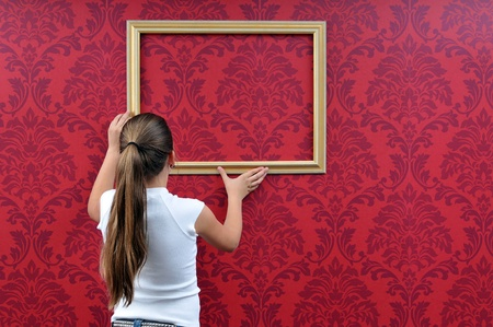 girl hangs up a picture frame Stock Photo - 10089809