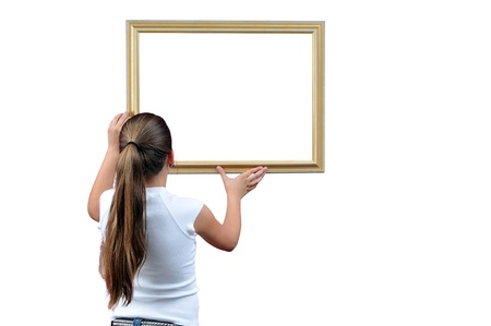 hangs: girl hangs up a picture frame