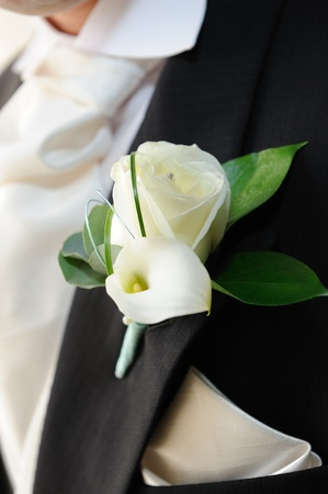 buttonhole: Grooms white roses and white lily in buttonhole. Stock Photo