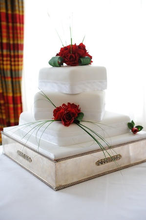 Wedding cake with red roses at reception.