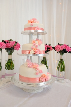 Three tier wedding cake with peach coloured detail.