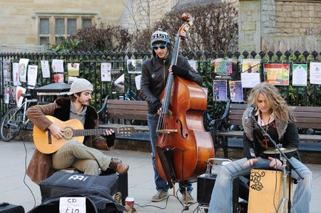 cambridge: Cambridge, England - February 19, 2012: Buskers play music on the street in the city centre. Editorial