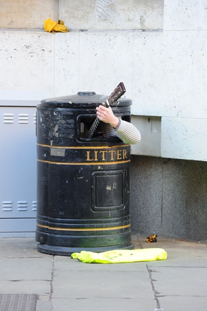Cambridge, England - February 19, 2012: A busker inside a trash bin plays guitar.