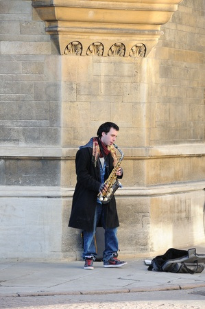Cambridge, England - February 19, 2012: A musician plays saxophone on the street in the city. Editorial