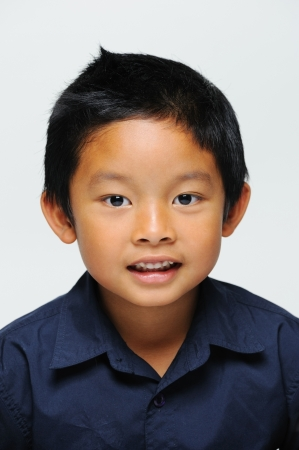 mischevious: Asian boy looking at camera and smiling