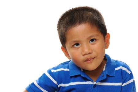 mischevious: Asian boy wearing blue shirt looking naughty