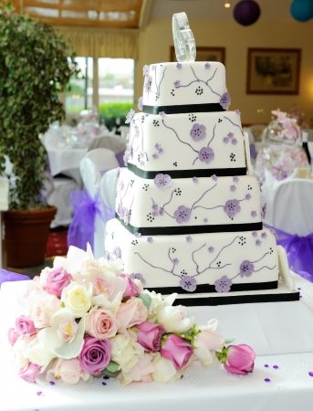 Purple wedding cake with brides bouquet at reception photo