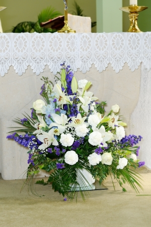 Purple and white flowers decorate church on wedding day