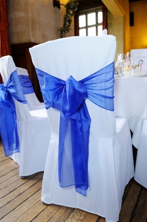 Blue ribbon chair cover tied in bow at wedding reception Stock Photo - 15974188