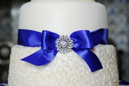 Blue ribbon decorates wedding cake at reception