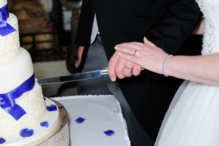Closeup of bride and grooms hands cutting cake and showing rings photo
