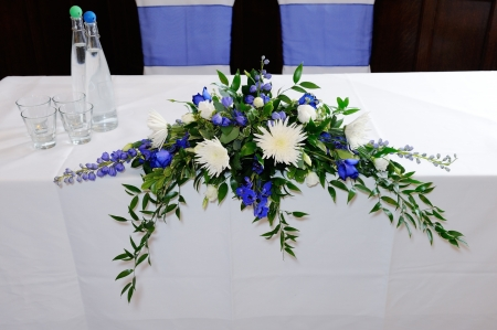 floral arrangement: Wedding ceremony table decorated with blue and white flowers Stock Photo