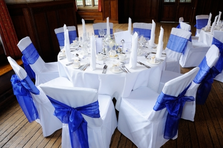 dining table and chairs: Table and chairs decorated in blue and white at wedding reception