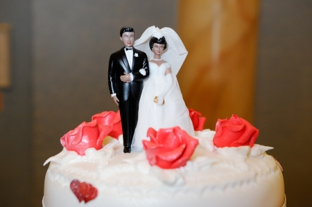 Ethnic Bride and groom decorate wedding cake photo