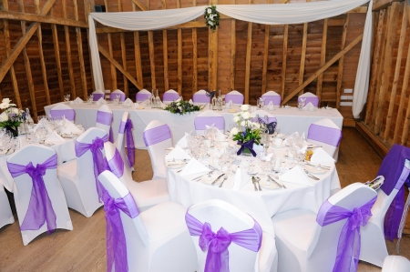 Wedding reception setting with white and purple decorations