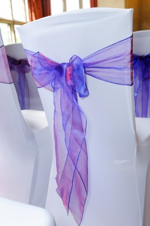 A chair covered with white and purple ribbon Standard-Bild