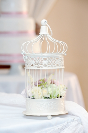 reception table: White cage with roses decorates a wedding reception Stock Photo
