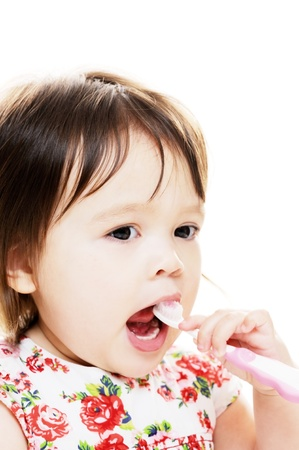Little girl enjoys brushing her teeth photo