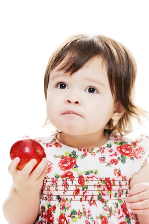 Baby girl tasting a red fresh red apple