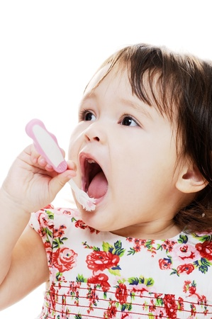 tooth cleaning: Little girl brushing teeth with pink toothbrush Stock Photo