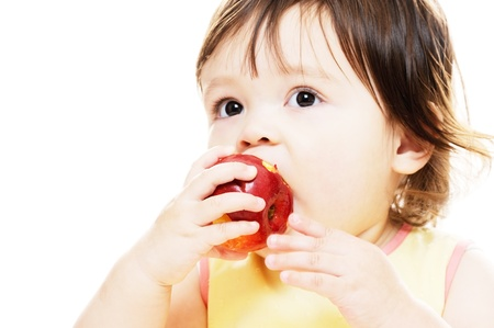 Little girl eating a fresh red apple photo