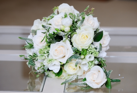 buttonhole: Close-up of brides flowers and grooms single rose on wedding day Stock Photo