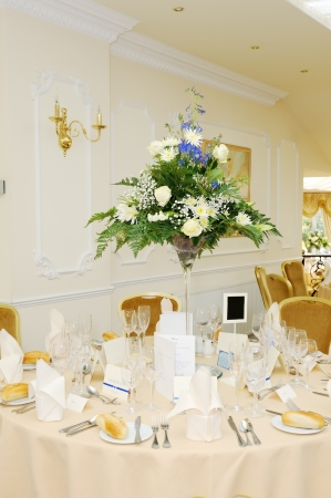 Weding reception table decorated with flowers with yellow tablecloth