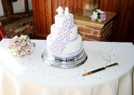 Wedding cake and brides bouquet with decoration and knife photo