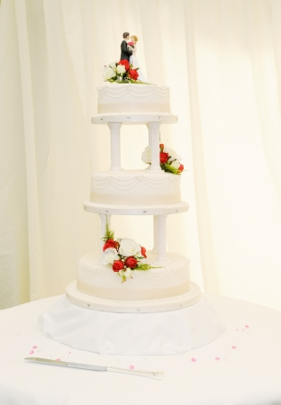 Wedding cake closeup at reception is white with bride and groom topper Stock Photo - 19356253