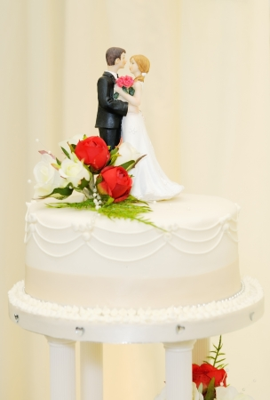 Wedding cake with bride and groom topper closeup detail photo