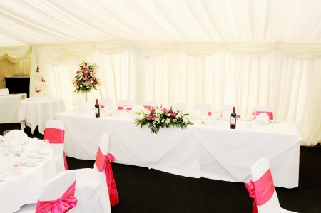 Wedding reception decorations inside marquee showing flowers and cake