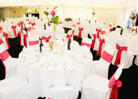 wedding chairs: Wedding reception inside marquee with flowers and pink ribbon for decoration Stock Photo