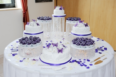 Huge wedding white and purple wedding cake at reception decorated with petals and butterflys photo