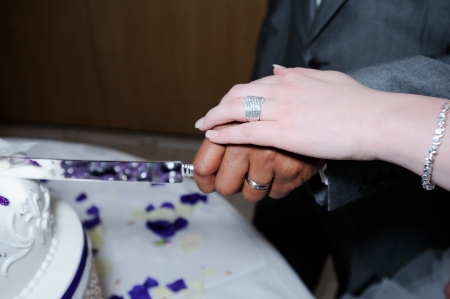 Bride and groom on wedding day cutting cake closeup showing rings and knife photo