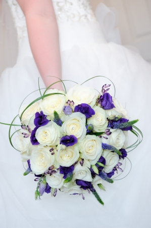 Bride holding bouquet of white rose and purple flowers on wedding day closeup Standard-Bild