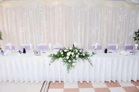 White and purple flowers decorate table at wedding reception