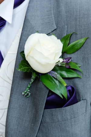 hankerchief: Grooms buttonhole closeup is white roseon wedding day