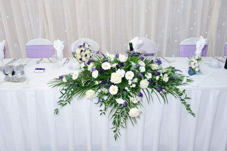 Table at wedding reception decorated with white and purple flowers Standard-Bild