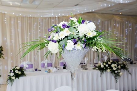 White and violet flowers decorate table at wedding reception