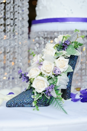 White rose in blue shoe decorate wedding reception with cake in background photo