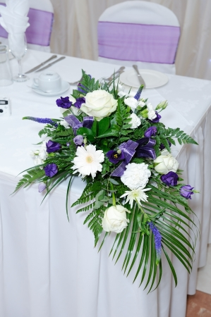 Purple and white flowers decorate table at wedding reception