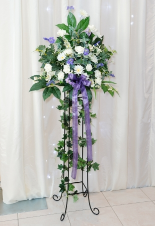 White and purple flower arrangement on stand at wedding reception