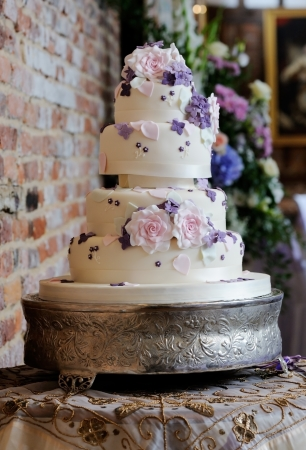 Wedding cake at reception has intricate decoration of pink and purple flowers