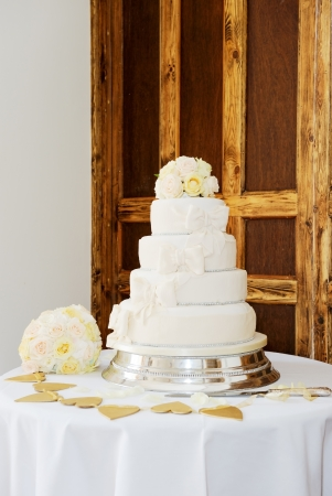 Wedding cake and brides bouquet of flowers at reception photo