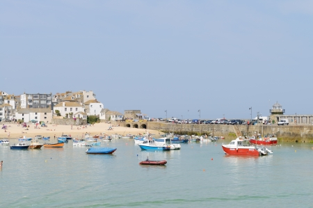 Fishing boats moored in the harbour of a cornish seaside town in the summer photo