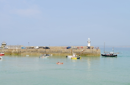 Lighthouse and boats visible in a harbour in St Ives, Cornwall, England on a sunny day in the summer  photo