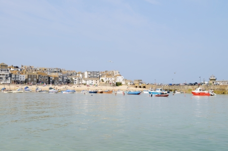 Cornish town by the sea on a sunny summer day, with boats moored in the harbour photo