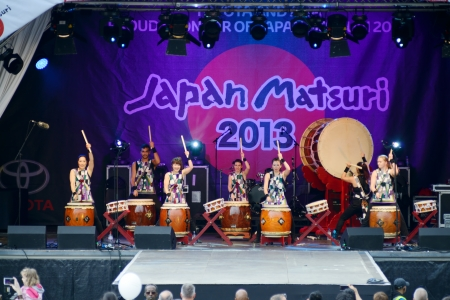 London, England - October 5, 2013      Japanese taiko drummers in traditional costume performing on stage at matsuri festival